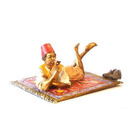 Orient. Bub mit Zigarre auf Teppich/Schuhe